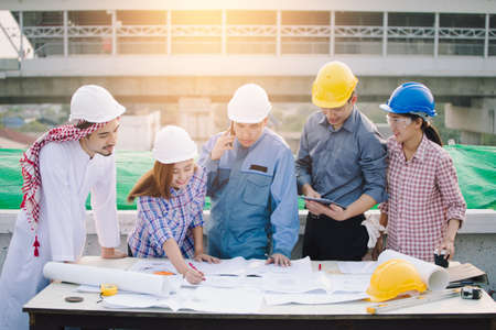 Business and Engineer working concept: Muslim Businessman, Engineer, Foreman and Worker discussing about plan of building site construction progression with layout paper at deck of their building.