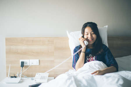 homeoffice: Attractive young woman lying on bed and talking on old retro telephone in the  hotel room Stock Photo