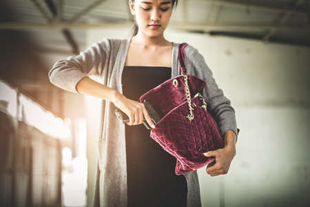swanky: Woman pulls a gun from her swanky purse. Conceal carry weapon for protection themselves concept. Selective focus to gun.