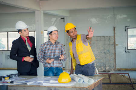 Management consulting and engineers and foreman working with stock 79947439 management consulting and engineers and foreman working with blueprint and drawing on work table for management business plan and construction malvernweather Gallery