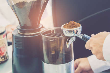 Hand of barista using tamper with ground coffee into portafilter in cafe for prepare to make espresso coffee.