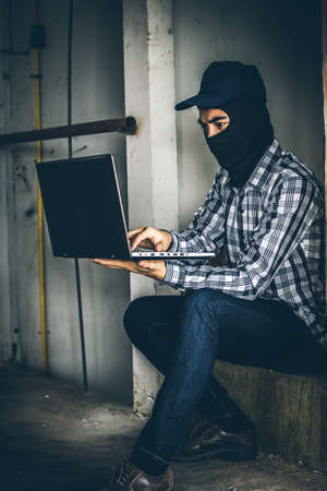 cyber terrorism: computer hacker of terrorist stealing information with laptop in abandoned building. Low key photo.