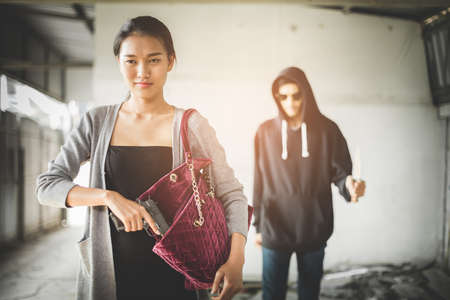 swanky: Woman pulls a gun from her swanky purse while the thief stood in the back. Conceal carry weapon for protection themselves concept. Selective focus to gun. Stock Photo