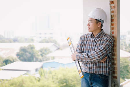 Engineer holding level measuring instrument and standing on old building.