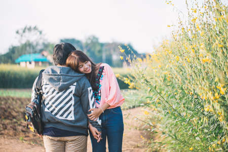 Young couple are happy and standing on a meadow in the morning on winter season. Green and yellow grass on background.
