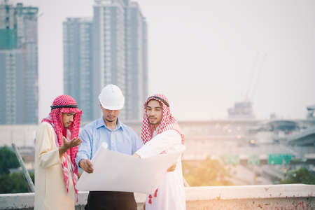 Muslim Business and Engineer working concept: Engineers and two Muslim businessman discussing about plan of building site construction progression with layout paper at deck of their building.