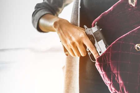 女性は、彼女の粋な財布から銃を引っ張る。身を隠すため保護のため運ぶ武器の概念。銃を選択と集中。