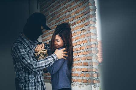 어두운 곳에서 무서워하는 여성을 공격하는 테러리스트와의 성적 학대. 강간 및 성적 학대 개념입니다.