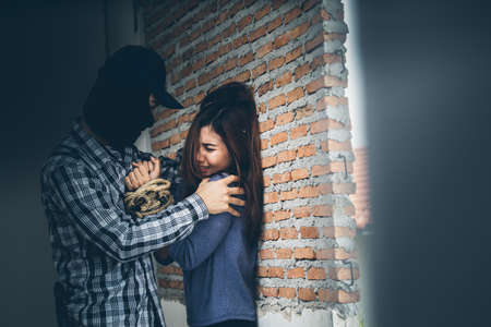 Sexual abuse with a terrorist attacking a scared woman in a dark place. Rape and Sexual abuse concept.