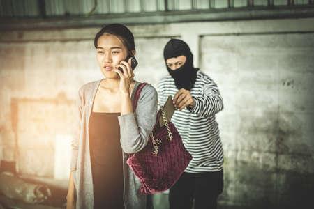 delincuencia: Ladrón que roba la carpeta de las mujeres del bolsillo mientras que ella que juega el teléfono elegante en manera lateral. Criminal y robo para las mujeres concepto. Foto de archivo