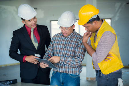 Management consulting and engineers and foreman working with stock 79569094 management consulting and engineers and foreman working with blueprint and drawing on work table for management business plan and construction malvernweather Choice Image