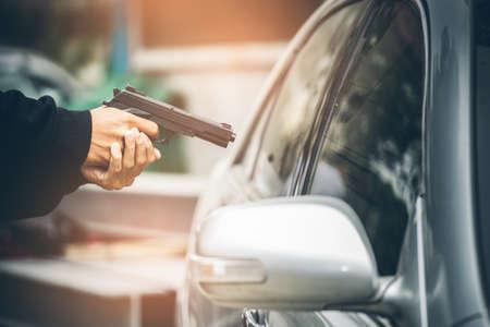Een robber gekleed in zwart die een geweer wijst op een bestuurder in een auto. Car thief concept.
