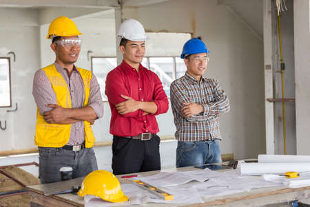 Portrait of confident foreman labor and engineer standing and smiling with safety helmet at old buildings in their job site. Stock Photo