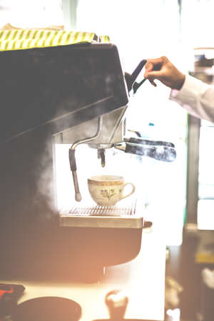 Barista releasing stream by cofee machine with cup for prepares espresso coffee in his coffee shop.
