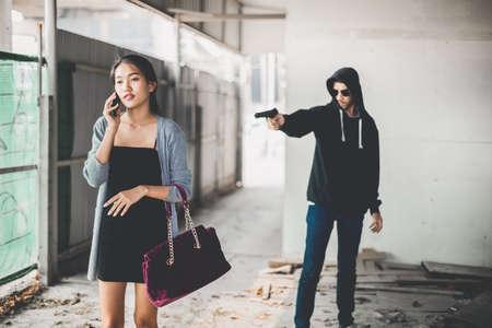 delincuencia: El hombre en la sudadera con capucha que roba y que amenaza con el arma a la mujer joven asustada. Criminal y robo para el concepto de mujer.