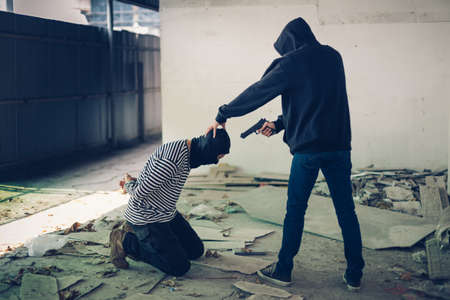A terrorist man in hood holding gun kidnapping a man for a hostage in abandoned building. Rape, terrorism, crime, violence, robbery and killer conception.