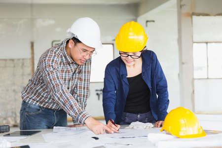 Management consulting or Engineer and labor woman working with blueprint and drawing on work table in for management business plan and construction site project.