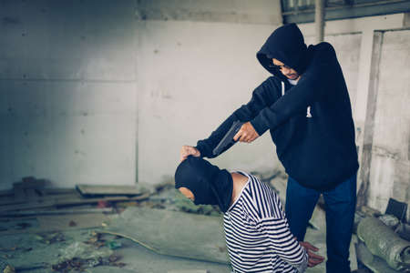 A terrorist man in hood holding gun kidnapping young man for a hostage in abandoned building. Rape, terrorism, crime, violence, robbery and killer conception.