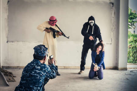 A terrorist man in mask holding gun kidnapping young women for a hostage in abandoned building and The soldier are helping.Rape, terrorism, crime, violence, robbery and killer of women conception.