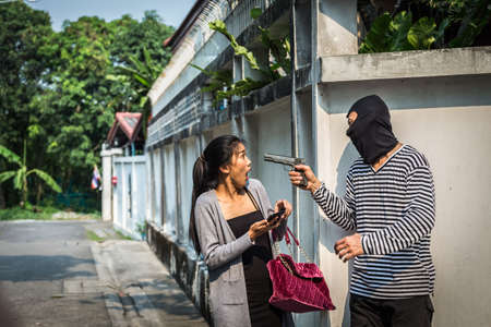 phon: Man in hoodie robbing and threatening with gun to frightened young woman While use on the phone. criminal and robbery for woman concept.