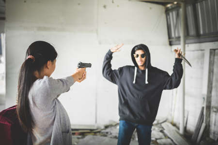 Woman pointing a shotgun to thief while the thief are coming in for robbery. Concealed carry weapon for protection themselves concept.