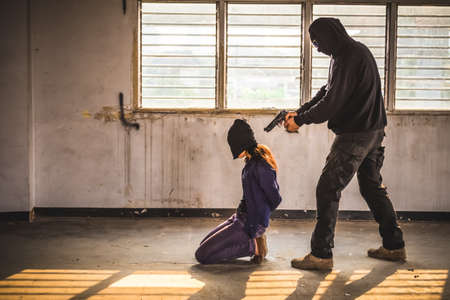 A terrorist man holding gun kidnapping young women for a hostage in abandoned building. Rape, terrorism, crime, violence, robbery and killer of women conception.