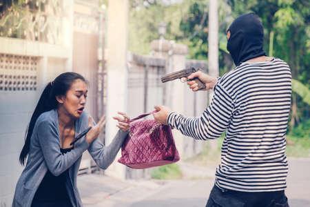 delincuencia: El hombre en la sudadera con capucha robando y amenazando con el arma a la mujer joven asustada Mientras que hablando por teléfono. criminal y robo para el concepto de la mujer.