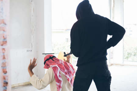 Murderers or terrorists or masked thief use guns(war weapon) and shooting to muslim man in abandoned building. War and terrorist purposes conception.