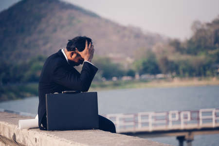 Back view of tired or stressed businessman in a suit with a briefcase and sitting on concrete of reservoir with mountains view. Unemployed businessman concept.