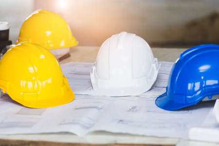The white, blue and yellow safety helmet stacking on table with the blueprint and measuring tools  at construction site for Engineer, foreman and worker. Safety first concept.