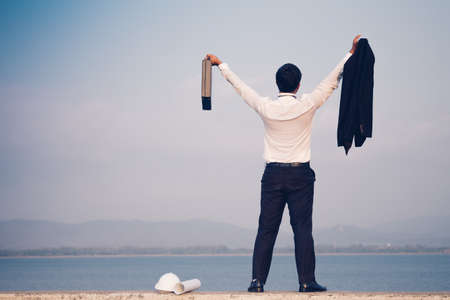 Back view of businessman in a suit with a briefcase and standing on concrete of reservoir with mountains view. Tired or stressed businessman concept.
