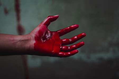 Halloween and horror concept. bloody hand in abandoned house. Photo with grain. Stock Photo
