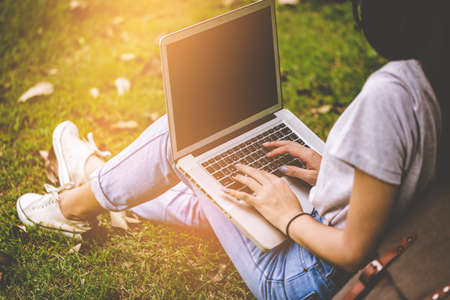 College student girl making report with laptop and listen to music via headphones, sitting at garden. Outdoor education concept.