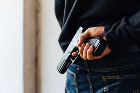 Criminal and robbery concept. Robber pulls out a gun tucked in his jean.