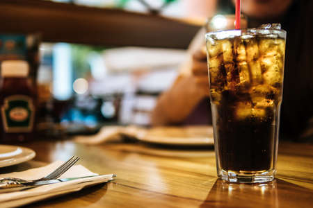 Soft drink with Ice and red straw in glass and blurred woman in background at restaurant