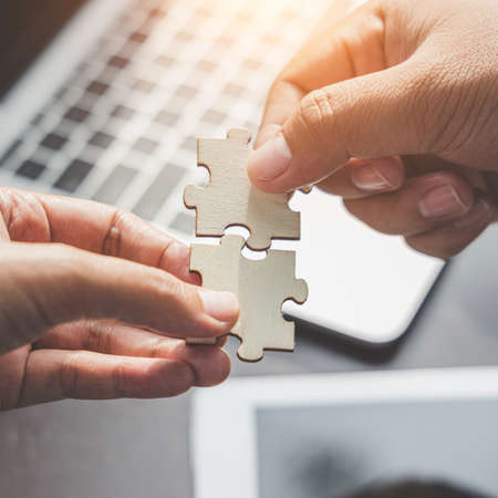 Business solutions, Businesswoman hand connecting jigsaw with businessman hand. success and strategy and partner concept.