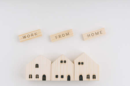 Top view of STAY HOME wording on wooden blocks and wooden house and wooden toy. White background. Stay home concept. Coronavirus COVID-19 outbreak advice