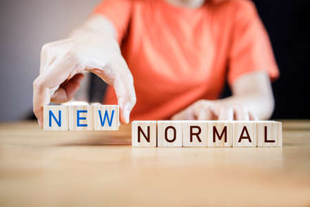 Woman's hand putting wooden cubes with concept new or next normal. New normal life after COVID crisis impact around the world business. Changing human lifestyle after the world economy is disrupted.