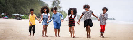 Funny vacation. Children or kids playing and romp together at the beach on holiday. Having fun after unlocking down the city from COVID19. Seven African American kids. Ethnically diverse concept 版權商用圖片