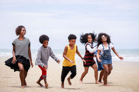Funny vacation. Children or kids playing and romp together at the beach on holiday. Having fun after unlocking down the city from COVID19. Seven African American kids. Ethnically diverse concept 스톡 콘텐츠