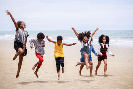 Vacances amusantes. Des enfants ou des enfants jouent et s'amusent ensemble à la plage en vacances. S'amuser après avoir déverrouillé la ville de COVID19. Sept enfants afro-américains. Concept ethniquement diversifié Banque d'images
