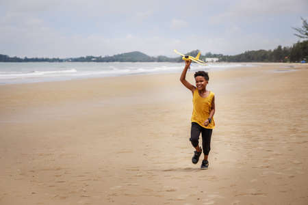 Happy colored boy and African American boy playing yellow toy airplane and running by wearing yellow sweater. Having fun on beach after unlock down city from COVID19. concept of dreams and travels