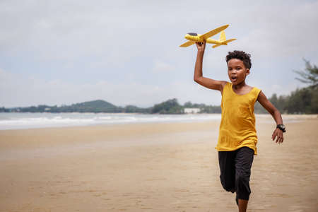 Happy colored boy and African American boy playing yellow toy airplane and running by wearing yellow sweater. Having fun on beach after unlock down city from COVID19. concept of dreams and travels Stock fotó
