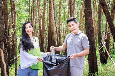 CSR activity. Corporate Social Responsibility. Two volunteers, Asian male and female, are helping to pick up waste by black garbage bags in park and conservation forest. Environmental problem concept. 免版税图像
