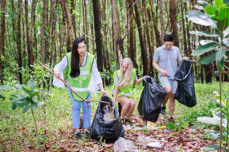 CSR activity. Corporate Social Responsibility. Three volunteers, Asian male, female and Caucasian are helping to pick up waste by garbage bags in park conservation forest. Environmental problem.