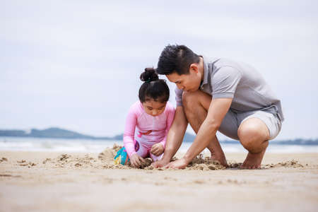 Happy family. Happy vacation holiday. Happy father and daughter are building a sandcastle on the tropical beach and have fun together in summer. Relaxation in vacation in the summer concept. Standard-Bild
