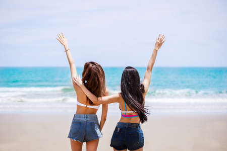 Outdoor summer portrait of the back image of two Asian beautiful girls in a sexy bikini standing on the beach in summer. teenage girls best friends. sexy buttocks. concept vacation,  holiday in summer