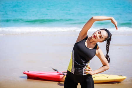 young Asian woman is stretching or warm-up her body before exercise by running on the beach in the morning and get fresh air. female fitness model portrait. Concepts of exercise and good health. Standard-Bild - 151093611