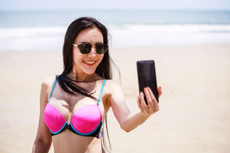 Beautiful Asian woman in a bikini is performing live stream on social media applications by smartphone while she relaxing on the beach on holiday. Social network and lifestyle and vacation in summer