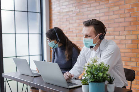 young women and man call center wear headset and mask working with laptop while consulting customers with online problems. support operator service business representative concept. online marketing